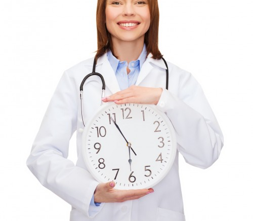 smiling female doctor with wall clock
