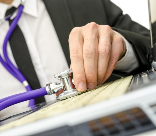 Close up of repairman holding stethoscope of laptop keyboard