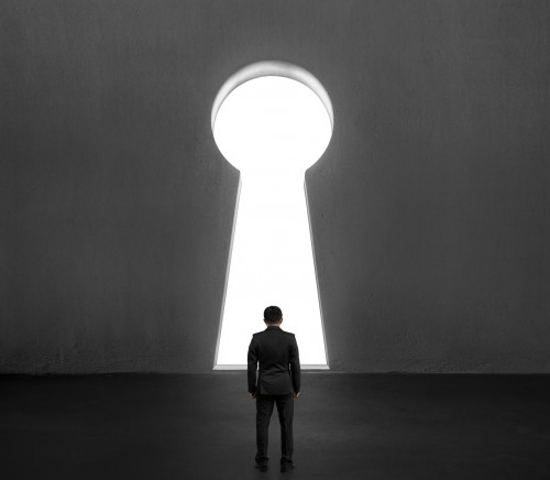 Man standing in front of key shape door