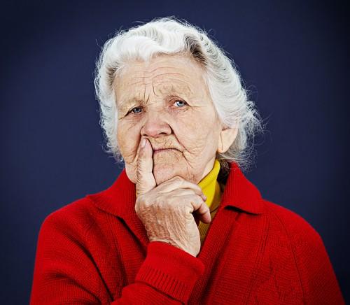 Portrait skeptical old, elderly woman on dark background