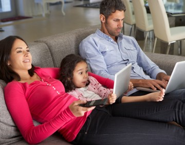 Family On Sofa With Laptop And Digital Tablet Watching TV
