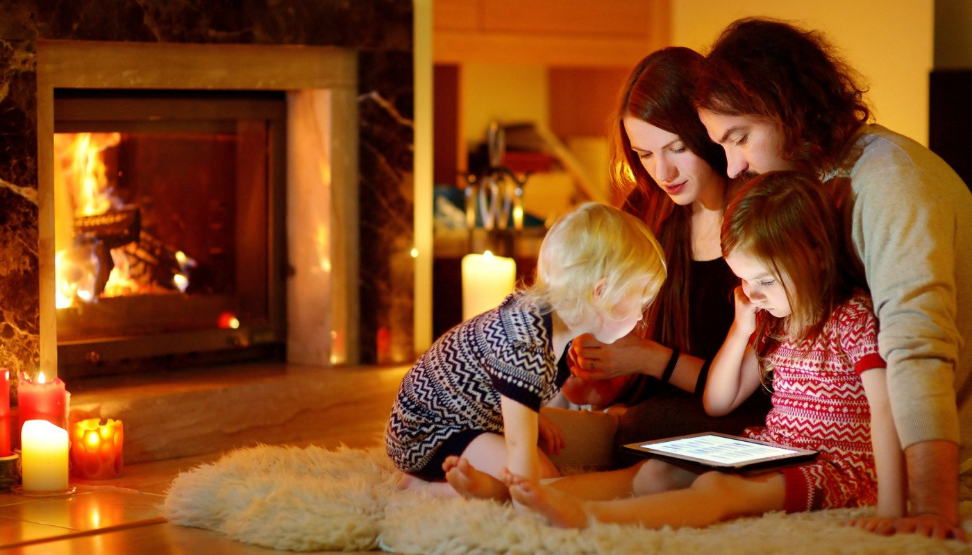 Happy family using a tablet pc by a fireplace