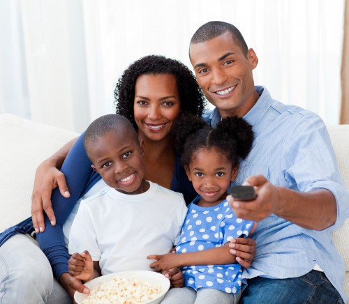 Smiling Afro-american family eating popcorn and watching TV