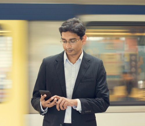 Asian Indian businessman texting using smartphone while waiting train at railway station