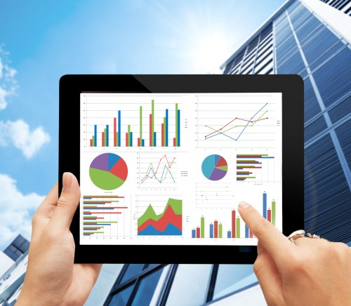 hand holding digital tablet  with analyzing graph against office buildings with sun