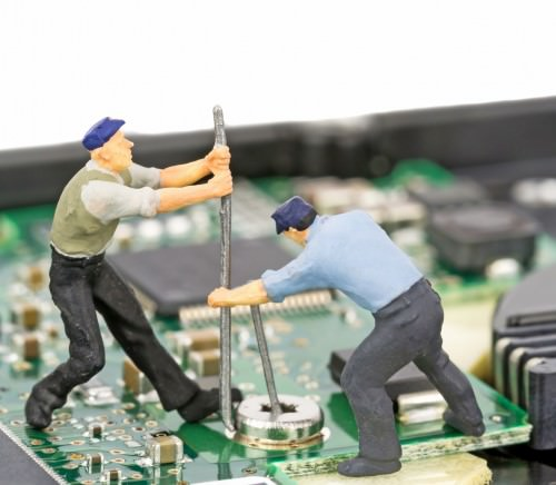 Miniature engineers repairing a computer hard drive