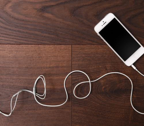 Smart phone and earphones on wooden surface