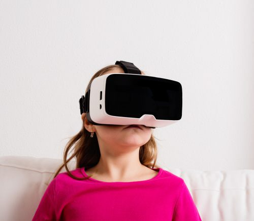 Cute little girl in pink t-shirt wearing virtual reality goggles. Studio shot, white couch, copy space
